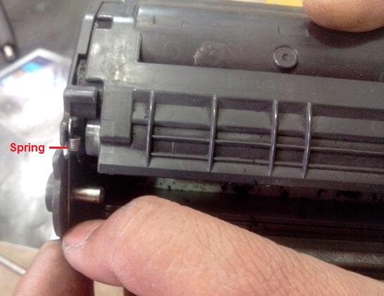 پس از خارج کردن پین از هر دو طرف کارتریج تونر، شما باید فنر را همانطور که نشان داده شده است خارج کنید