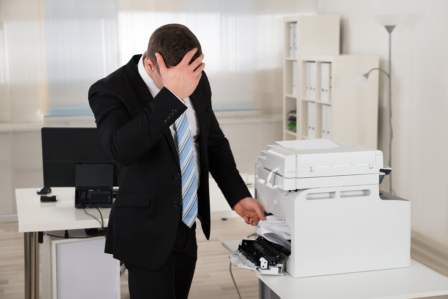 Irritated Businessman Looking At Paper Stuck In Printer