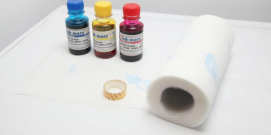 یک رول دستمال کاغذی، و مقداری نوار چسب را بر روی  یک سطح کار بزرگ و صاف، مانند یک میز قرار دهید